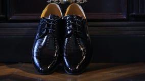 Le scarpe nuziali nere brillanti stanno sul pavimento vicino al guardaroba di legno archivi video