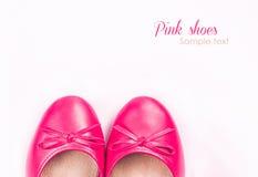 Le scarpe rosa su fondo bianco con il campione mandano un sms a Fotografia Stock
