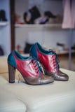 Le scarpe rosse e verdi si trovano sulla stanza frontale di negozio Fotografia Stock