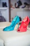 Le scarpe rosse e verdi si trovano sulla stanza frontale di negozio Immagini Stock Libere da Diritti