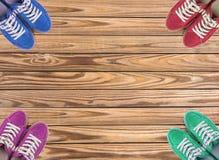 Le scarpe variopinte hanno messo su fondo di legno con lo spazio della copia Vista superiore Immagine Stock Libera da Diritti
