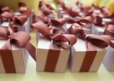 Le scatole rosse ed a strisce con i regali hanno legato gli archi su bianco Fotografie Stock