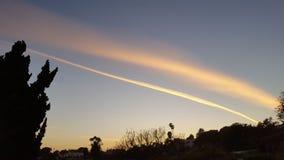 Le scie di condensazione dipingono così i cieli di sera di caloria Immagini Stock Libere da Diritti