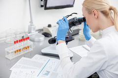 Le scientifique assez jeune regarde des bactéries plus étroites image stock