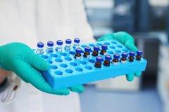 Le scientifique de laboratoire tient une boîte en plastique avec des échantillons de liquide transparent dans les fioles photos stock