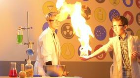 Le scientifique fait des expériences avec le feu avec le petit garçon dans le laboratoire banque de vidéos