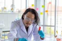 Le scientifique futé asiatique d'homme examine le tube à essai images libres de droits