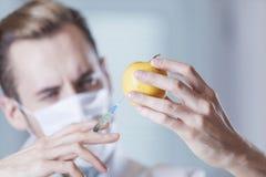 Le scientifique injecte Apple avec une seringue photo libre de droits