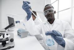 Le scientifique masculin avec un flacon fait un essai dans le laboratoire photographie stock