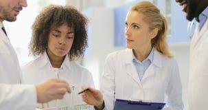Le scientifique sérieux Woman Discuss Chemicals avec son équipe faisant des chercheurs de notes groupent le travail dans le labor clips vidéos