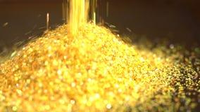 Le scintille dorate cadute dell'oro della polvere di scintillio cadono ad un mucchio stock footage
