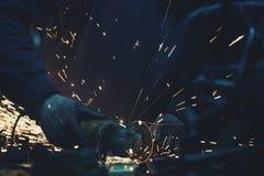 Le scintille e la smerigliatrice di angolo con le scintille intorno hanno usato per tagliare il tubo d'acciaio in un'officina scu Immagine Stock Libera da Diritti
