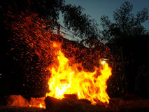 Le scintille rimbalzano fuori da un falò alla notte dopo un ceppo gettato in  Fotografie Stock