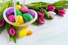 Le scintillement multicolore de Pâques eggs dans le panier jaune et les tulipes rouges Photographie stock