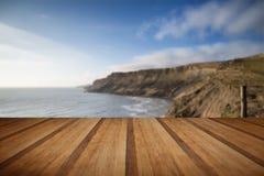 Le scogliere abbelliscono l'allungamento fuori al mare con il pavimento di legno delle plance Immagine Stock