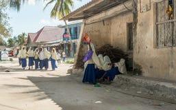 Le scolare si avvicinano alla vecchia scuola del villaggio a Zanzibar Fotografie Stock Libere da Diritti