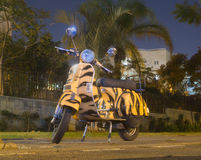 Le scooter comme le Vespa s'est garé sous la lanterne la nuit Image libre de droits
