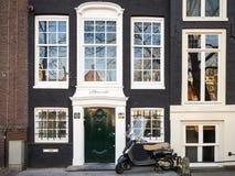 Le scooter de Vespa se tient garé près de la vieille maison vivante à Amsterdam Photos libres de droits