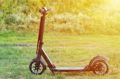 Le scooter noir de coup-de-pied de pliage, se ferment vers le haut des pièces, effet de lumière du soleil photos stock