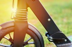 Le scooter noir de coup-de-pied de pliage, se ferment vers le haut des pièces, roue avant, effet de lumière du soleil photos stock