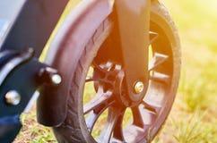 Le scooter noir de coup-de-pied de pliage, se ferment vers le haut des pièces, roue avant, effet de lumière du soleil photo libre de droits
