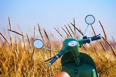 Le scooter s'est garé dans un domaine de blé près de la plage photos stock
