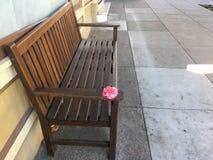 Le ` se reposent svp avec moi et soient soulagés, ` Rose délicatement offerte, du banc photos libres de droits