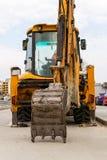 Le seau d'excavatrice se repose sur l'asphalte Excavatrice jaune avec un seau abaissé sur une rue de ville un jour non-travaillan photos stock