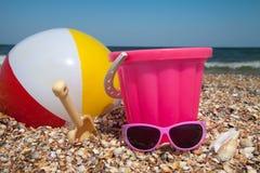 Le seau de l'enfant, la boule et d'autres jouets sur la plage tropicale contre le ciel bleu Photos libres de droits