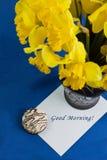Le seau de narcisse fleurit dans le vase, enveloppe sur le fond bleu Image libre de droits