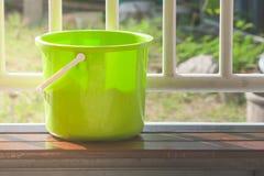 Le seau ou le seau d'eau en plastique vert a mis dessus la longue chaise en bois avec la barrière en acier blanche à l'arrière-pl image libre de droits