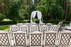 Le sedie bianche stanno nelle file prima dell'altare di nozze Fotografia Stock