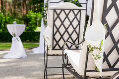 Le sedie bianche stanno nelle file prima dell'altare di nozze Immagine Stock Libera da Diritti