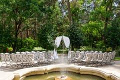 Le sedie bianche stanno nelle file prima dell'altare di nozze Immagine Stock