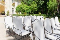 Le sedie bianche stanno nelle file prima dell'altare di nozze Fotografie Stock