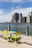 Le sedie colorate davanti alle costruzioni di Manhattan e di East River Immagini Stock Libere da Diritti