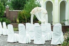 Le sedie coperte di panno bianco stanno nella parte anteriore di Al di nozze Immagini Stock