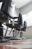 Le sedie del barbiere nel salone di capelli fotografia stock