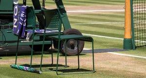 Le sedie del ` dei giocatori con l'asciugamano hanno ripiegato la parte posteriore e un ombrello verde e porpora sulla terra L'as immagini stock libere da diritti