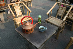 Le sedie di bambù attendono i patroni per bere il tè verde cinese dal vaso di rame Fotografia Stock