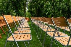 Le sedie di legno stanno esterne nel parco nella pioggia Sala vuota, erba verde, alberi e gocce di acqua fotografie stock