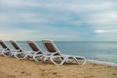 Le sedie di plastica bianche su Mar Nero costeggiano Zatoka Ucraina Fotografia Stock