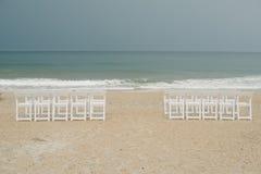 Le sedie hanno installato sulla spiaggia per una cerimonia di nozze tempestosa. Immagine Stock