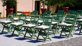 Le sedie verdi sono installate nelle file per un evento immagine stock