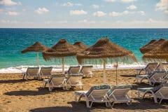 Le sedie vuote sulla spiaggia sabbiosa aspettano gli Sun-adoratori Fotografia Stock