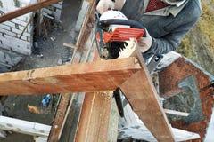 Le seghe del costruttore sul tetto della motosega Travi del tetto fotografie stock