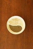 Le sel brut et la terre poivrent dans la petite soucoupe en Ying et en Yang Photographie stock libre de droits