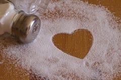 Le sel et le coeur forment sur la table en bois avec le dispositif trembleur de sel Images stock