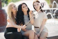 Le selfie d'été de trois amis en parc près de la fontaine Image libre de droits