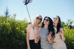 Le selfie d'été de trois amis en parc vert Photographie stock